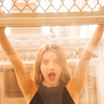 Giovane donna colpita che sta dietro la finestra di vetro