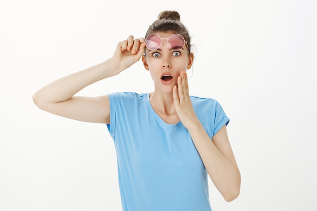 Shocked young woman take-off sunglasses and gasping worried or concerned