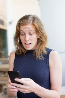 Shocked young woman using smartphone outdoors