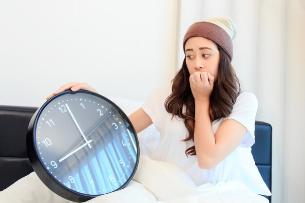Shocked young woman waking up with alarm on her bedroom. concept for healthy and business