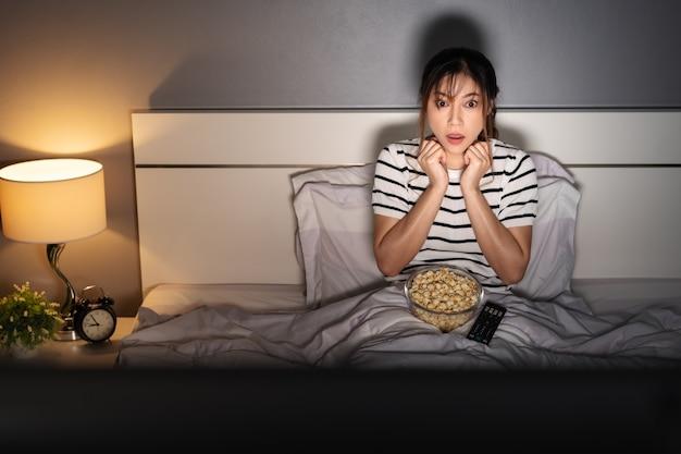 Шокированная молодая женщина смотрит фильм на кровати ночью