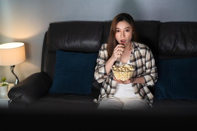 밤에 소파에서 tv 영화를 보고 충격을 받은 젊은 여성