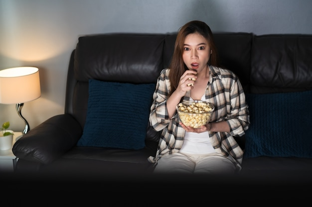 Shocked young woman watching tv movie on sofa at night