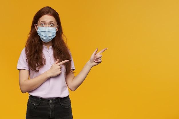 黄色の壁に隔離されたコピースペースで横に離れて両手で2本の指で見て、指している医療用保護マスクを身に着けているショックを受けた若い女性