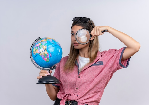 A shocked young woman wearing red shirt in sunglasses holding a globe while looking at it with magnifying glass on a white wall