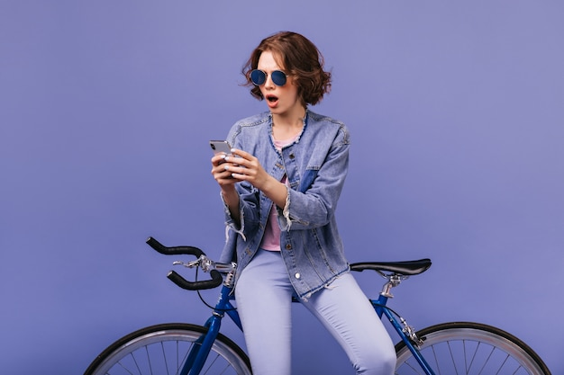 Shocked young woman with brown hair looking at phone screen. spectacular female model sitting on bicycle and using her cell.
