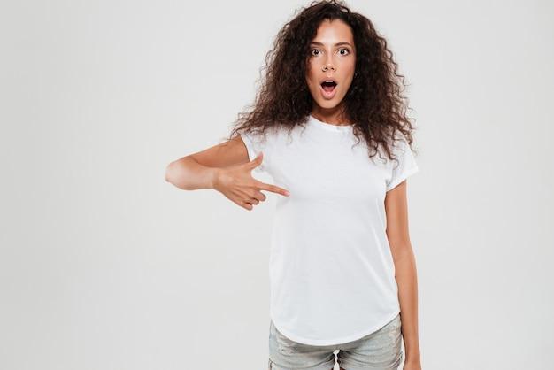 Шокирован молодая женщина с вьющимися волосами