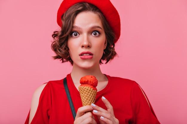 アイスクリームを食べる暗いウェーブのかかった髪のショックを受けた若い女性。おいしいデザートを持っているロマンチックなヨーロッパの女の子。