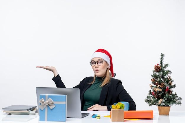 Scioccato giovane donna con cappello di babbo natale e occhiali seduti a un tavolo con un albero di natale e un regalo su di esso su sfondo bianco