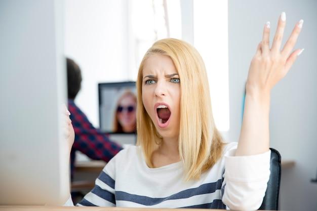 컴퓨터에서 작업하는 충격 된 젊은 여자