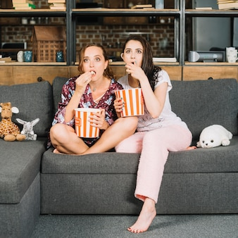 Shocked young women sitting on sofa watching television