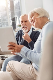 Shocking content. charming elderly lady showing her husband a video on the tablet while he looking shocked by it and tugging at his beard