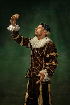 Shocking food. portrait of medieval young man in vintage clothing with wooden frame on dark background. male model as a duke, prince, royal person. concept of comparison of eras, modern, fashion.