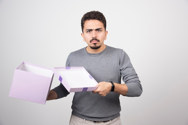 Uomo scioccante che apre una scatola viola su un muro bianco.