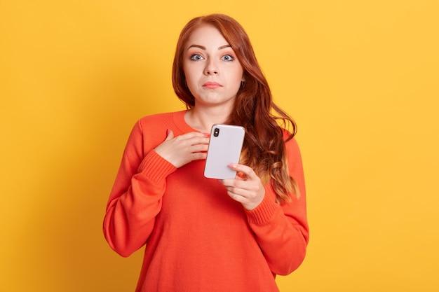 衝撃的なニュース!スマートフォンでセンセーショナルなニュースを読んでオレンジ色のカジュアルセーターで驚いた若い女性の肖像画を間近します。