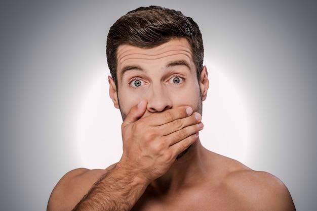 Шокирующие новости. портрет потрясенного молодого человека без рубашки, смотрящего в камеру и прикрывающего рот рукой, стоя на сером фоне