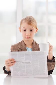 Шокирующие новости. удивленная маленькая девочка в строгой одежде читает газету и держит чашку, сидя за столом