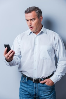 Shocking news. surprised mature man in shirt holding mobile phone and looking at it while standing against grey background