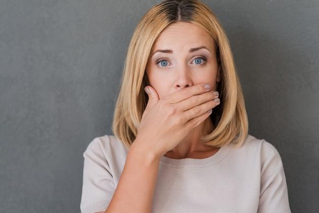 衝撃的なニュース。手で口を覆い、カメラを見つめて驚いた成熟した女性