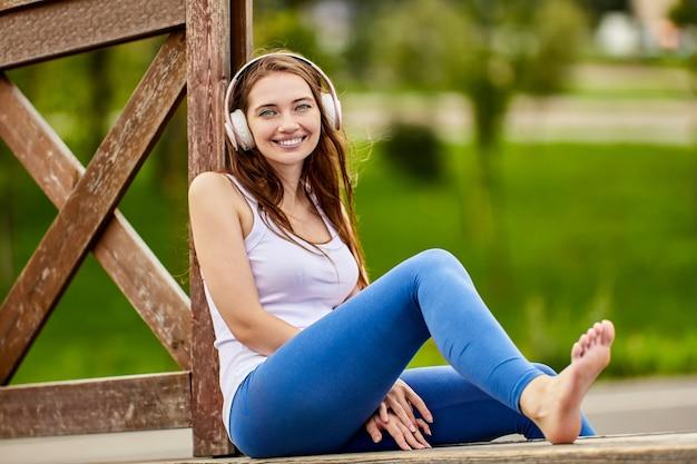 Счастливая женщина без обуви в беспроводных наушниках сидит на открытом воздухе