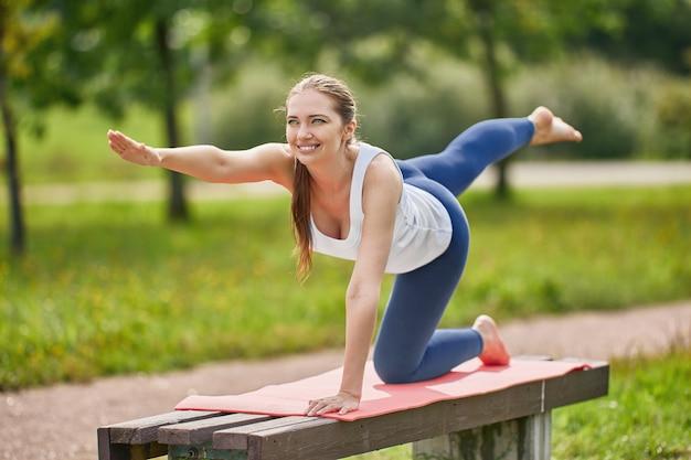 Женщина без обуви делает упражнения йоги на скамейке в парке