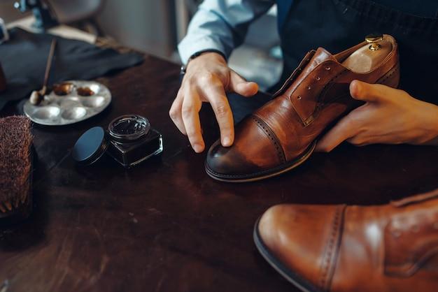 Shoemaker applies black shoe polish, footwear repair service. craftsman skill, shoemaking workshop, master works with boots, cobbler shop