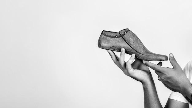 Shoemaker holding wooden footwear. man hands holding last shoe.