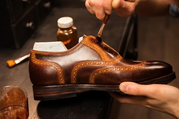 Сапожник в мастерской по изготовлению обуви