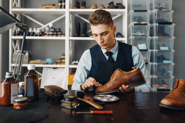 Shoemaker polishes the shoe, footwear repair service. craftsman skill, shoemaking workshop, master works with boots, cobbler