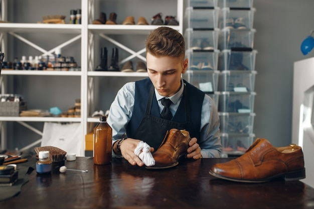 Shoemaker polishes the shoe