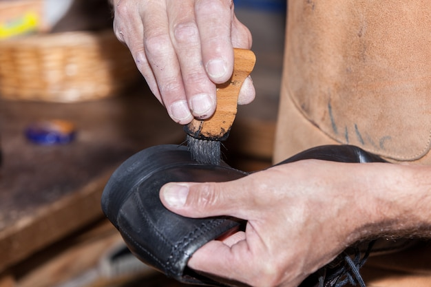 The shoemaker puts shoe polish