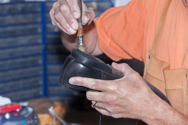 The shoemaker repairs a shoe