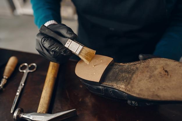 Shoemaker smears glue to the shoe