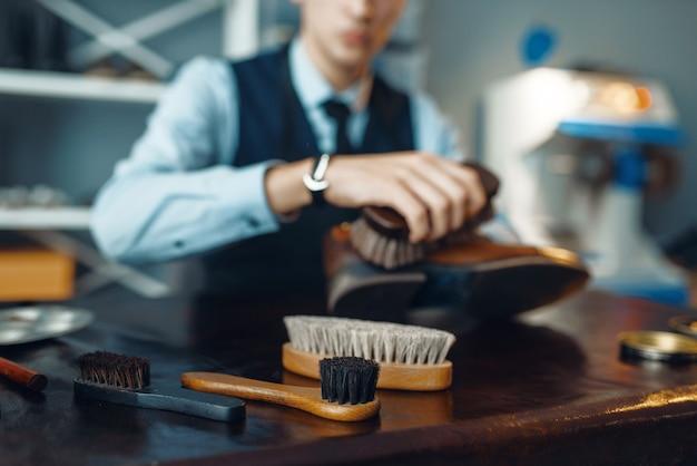 Shoemaker wipes black shoe polish, footwear repair service. craftsman skill, shoemaking workshop, master works with boots, cobbler shop