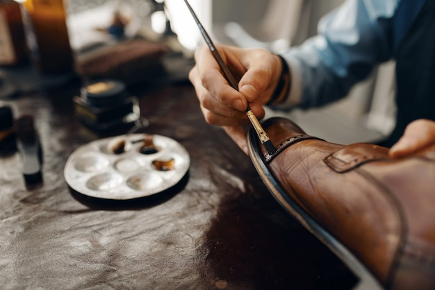Shoemaker with brush tints shoes, footwear repair service. craftsman skill, shoemaking workshop, master works with boots, cobbler