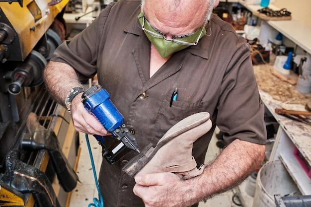 マスクを使ってコロナウイルスの日に取り組んでいる靴屋