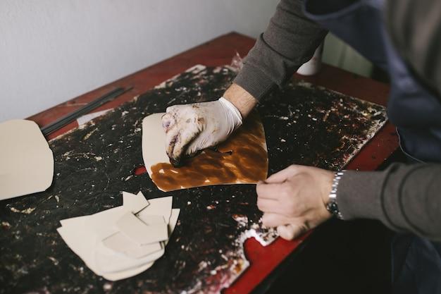 Shoemaker in workshop making leather shoes.