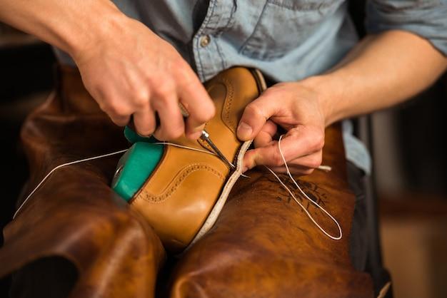 Shoemaker in workshop making shoes