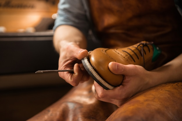 Shoemaker in workshop making shoes