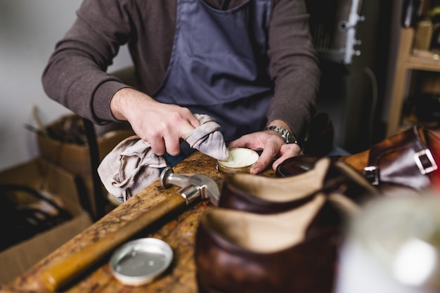 Shoemaker in workshop polishing new handmade beautiful leather shoes.