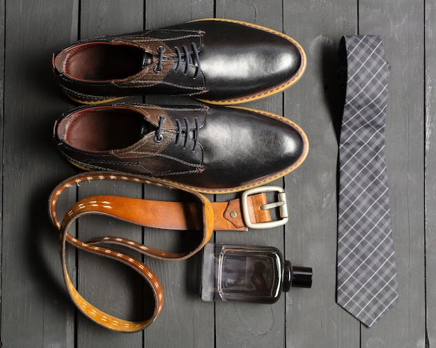 Shoes and accessories for men lay on the wood floor