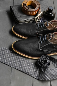 Shoes and accessories for men lay on the wooden floor