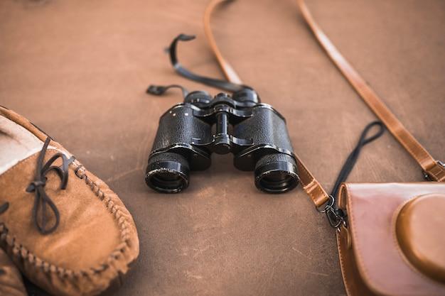 Обувь и сумка для камеры возле бинокля