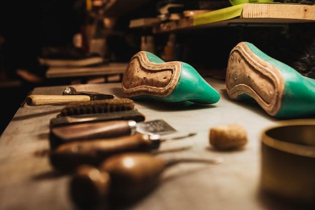 Обувь и инструменты на столе в обувной мастерской.