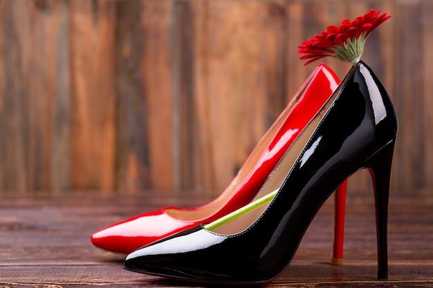 靴と赤い花。ガーベラと木の靴。あなたの完璧な靴を選択してください。ファッションは人生の一部です。