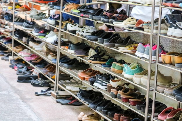 Shoes are organized in an orderly manner on shelves inside a temple