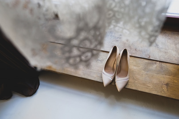 Shoes of the bride on background of wedding veils.