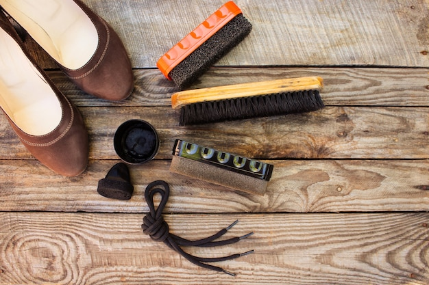 Shoes and care products for footwear on wooden table
