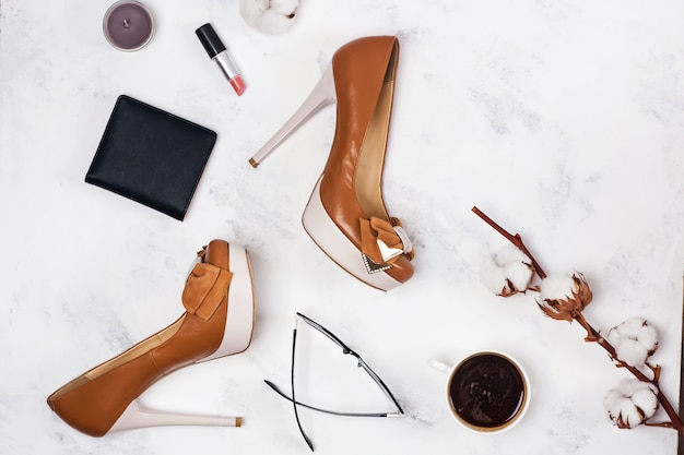 Shoes, coffee, stylish accessories and cotton branch on the light marble background.