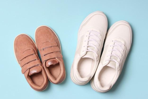 Обувь для детей и женские кроссовки на цветном фоне вид сверху